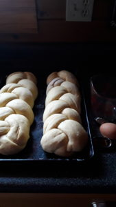 Two uncooked, braided egg bread loaves on pan, with fresh egg and measuring cup next to pan.
